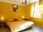 chambre jaune avec grand lit double
