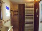 Salle de bain avec grande douche à l'italienne derrière la cloison .