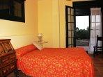 Habitación Planta Baja, Sala de estar, acceso a parcela y Porche.  Baño completo