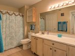 The en suite bathroom has a vanity with 2 sinks and a tub/shower combo.