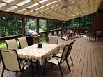 LARGE main floor deck with four rocking chairs, porch swing, table for 6, table for 4 and one for 2!
