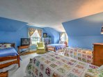 This room featuring a cable TV and four twin beds is the ultimate room for kids to hide out in and tell ghost stories...