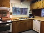 Fully equipped kitchen with dishwasher, stove, oven, refrigerator, blender, and coffee station.