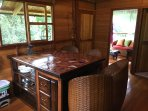 View of kitchen with comfortable, hand woven seating for 4, attached living area, bathroom & bedroom