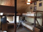 Sleeping Loft, with 4 longboy twin beds.  Shares bath with Fishing room. Overlooks main living area.