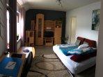 Wohnzimmer mit ausgeklappten Schlafsofa.