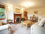 Large living room / dining room with windows to the front and side, with spectacular views over Fife