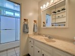 The adjacent full bathroom boasts a sleek vanity with ample counter space, as well as a separate shower-tub combination.