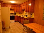 Full size kitchen is equipped with dishware, pots, pans and utensils.