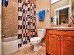Guest bathroom has tub / shower combination.