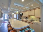 Additional seating can be found at the numerous bar stools wrapped around the kitchen island bar.