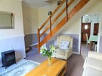 Welcoming lounge with stair case to upstairs