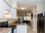 Galley kitchen is fully equipped and leads to private backyard.