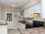 Galley kitchen leads to fenced private backyard.