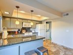 The kitchen features a wraparound countertop and well-kept appliances.