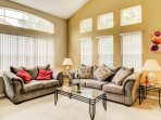 The living room boasts a plush couch and matching loveseat, along with tall bright windows!