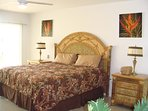 Master bedroom suite with king size bed and tropical decor