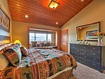 A king bed, vaulted ceilings, and an incredible view of the bay and mountains adorn the cozy bedroom.