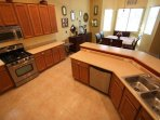 Kitchen area, with electric stove/oven, pantry and laundry room in hall leading to garage.