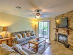 Comfortable furnishings, a decorative fireplace, and large sliding glass doors adorn the cozy living room.