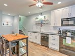 The generous kitchen features full sized appliances, an island with 2 seats, a four seat dining table and all the...