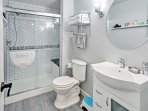 The designer bathroom features an over-sized walk-in shower with a bench seat and luxurious bath amenities.