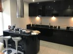 Kitchen with gloss black units and granite worktops