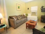 Bright living room with sofa sleeper and twin bed.