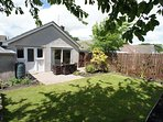 Fully enclosed back garden, perfect for pets, with outdoor furniture and lawn