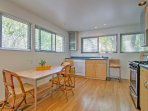 A wooden dining table makes for a comfortable spot to enjoy meals cooked in the fully equipped kitchen.