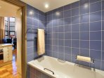 Tiled in Art Deco blue the bathroom has bath and shower