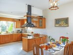 Open-plan fully equipped modern kitchen and the dining table