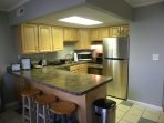 Fully equipped kitchen with dishwasher and bar stools for extra dining space