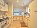 Prepare meals with ease in the fully equipped walk-through kitchen where all dishes, cooking, and baking utensils...