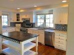 Updated kitchen with Miele dishwasher, KitchenAid gas stove, and fridge with ice maker