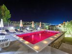 Pool in red color at night with a place in the background