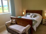 Bedroom 2 has a kingsize sleigh bed, views over the fields and an ensuite bathroom with rainshower.
