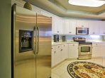The fully equipped, gourmet kitchen features sparkling corian counter tops, beautiful ceramic tile floor, and stainless...