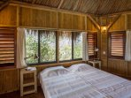 Double bedroom in the annex palapa with ceiling fan and a shared bathroom.