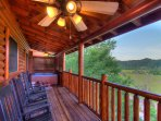 Beautiful main deck, ceiling fans, with lots of rocking chairs and hot tub on the main floor.