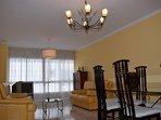 Amplio salón exterior con dos sofás de piel y zona de comedor