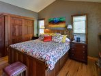 You'll love staying in the master bedroom with a king-sized bed and vaulted ceilings.