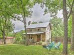 The tin roof, dramatic stone chimney, wooden porch, and garden bed will warm your heart, offering an authentic, Texas...
