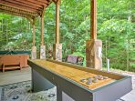 The home features a covered patio with a shuffleboard table and hot tub.