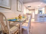 The dining table is adjacent to the kitchen and provides seating for 4.