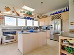 The fully equipped kitchen features stainless steel appliances and granite counters.