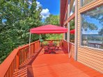 A covered patio directly beneath has a breezy swinging bench and additional outdoor furniture - the perfect spot to...