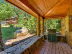 Outdoor sheltered deck with a grill