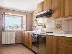 ampia cucina con fornelli e forno a metano, cappa, mobili con accessori cucina e frigo e congelatore