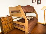 Loft with bunk beds - double on bottom and single on top, with dresser for storage.